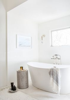 all-white bathroom with a freestanding tub