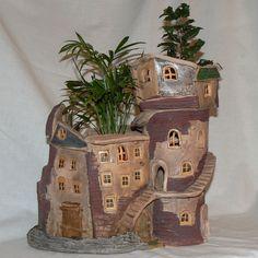 Domeček jako zámeček. Velký keramický květináč ve tvaru zámku je určený jako obal na květináč, nebo pro přímé vysázení květin. Věž může posloužit jako svícen. Do věže se hodí previslé kytky, do budovy vyšší. Váha 4321 g, výška 30 cm, délka 33 cm, šířka 25 cm.