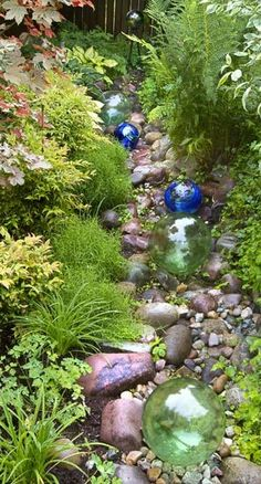 The rock-lined swale is both design feature and effective rain garden. It soaks up runoff in this wet, steep-slope garden. Glass floats further the look of a dry streambed.