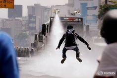 Un manifestante esquiva un chorro de agua durante un enfrentamiento con fuerzas de seguridad en #Caracas.