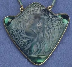 """Lalique 1913 'Femme Dans Les Fleurs' Pendant: 2"""" both high & wide triangle shaped w/additional rise on top metal-backed glass having a design of a reclining nude female figure amid foliage, cabochons at each corner, & metal attached rings connecting to the R.Lalique Pendant to the enameled baton link chain"""
