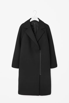 Made from wool with a smooth, silky lining, this elongated coat has a functional metal zip detail. Slightly oversized, it has full-length raglan sleeves, wide notched lapels and in-seam front pockets. It is secured with a hidden double-breasted fastening.