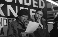 In this March 18, 1973 file photo taken in Wounded Knee, S.D., American Indian Movement leader Dennis Banks, left, reads an offer by U.S. government seeking to effect an end to the takeover of Wounded Knee. Looking on is AIM leader Carter Camp. Camp, a longtime activist with the American Indian Movement who was a leader in the Wounded Knee occupation in South Dakota, died Dec. 27, 2013, in White Eagle, Okla. He was 72.