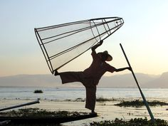 An Intha leg rower brandishes his conical fish trap at Inle Lake, Myanmar (Burma). Inle Lake, Boat, Fish, Legs, Dinghy, Boats, Ichthys, Bones