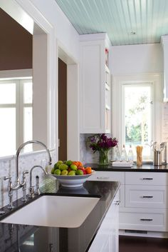 Kitchen with white cabinet and black gradient... I love the haint blue beadboard ceiling