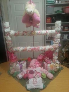 Daiper cake gift for girl. Showcases a jumping unicorn glow pillow over fence and grounds full of goodies. Created by Penny Casper