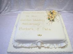 Large golden 50th wedding anniversary cake in ivory coloured icing.  Finished with simple honeysuckle floral detail and a piped message, the sides are finished with a garret frill and piping trail