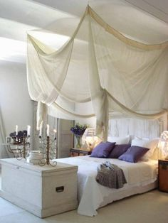 A pale rustic bedroom gets a feminine touch with a gauzy draped canopy hung from the ceiling. Fabric canopies can be created with an elaborate complicated look like this one, or in a more restrained tailored design.