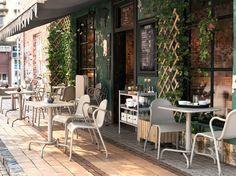 TUNHOLMEN bord og stoler i grå på en kafé med uteplass. Flere stoler og bord står stablet og slått sammen til side.