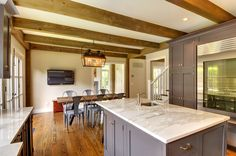 The barn homes post and beam kitchen looking toward the dining area. Beautiful marble countertops on Crown Point Cabinetry cabinets #floorplans.