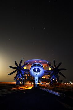 An E-2C Hawkeye assigned to the Wallbangers of Carrier Airborne Early Warning Squadron (VAW) 117 sits on the flight deck of the aircraft carrier USS Nimitz (CVN 68) at night.