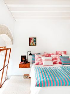 Get the Look: A Simply Bold Bedroom via @domainehome // Teal and coral striped bedding in a lofted bedroom.