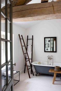 Baignoire pied de lion pour un rappel d'époque, échelle en bois pour les serviettes, petit meuble moderne en acier pour s'opposer au meuble d'appoint en bois. Du blanc pour le chic, des poutres apparentes en bois brut pour le côté vintage.