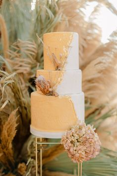 "From the editorial ""Spiritual Escapism Meets Future-Forward Bridal Inspiration in Greece."" Ranging from supple golds to creamy peaches, hay, butterscotch, and cornsilk, to Golden Marguerite for our cake, this shoot is filled with the dreamiest pops of color. Photography: @thanosasfis #weddingcake #cake #goldcake #cakeinspiration #weddingcakeidea"