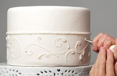 Person icing white cake