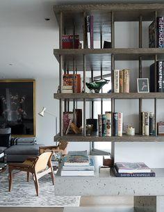 Open shelving over a concrete fireplace in the living room of London designer Tara Bernerd