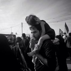 Shi'ite pilgrim carry his sleeping daughter on shoulders while walking towards Kerbala Iraq. Millions of Shi'ite pilgrims have started arriving in Iraq to attend Arbaeen 40th day period of mourning for 3rd Shia Imam & grandson of Prophet Muhammad (pbuh). Pilgrims walk from Najaf & many of them from Iran to Kerbala (80km) to attend Arbaeen. #Arbaeen #ArbaeenWalk2015 #NajafToKerbala #photojournalism #Iraq #pilgrim #journey #mourning #everydaykerbala #everydayiraq by munazzaanwaar