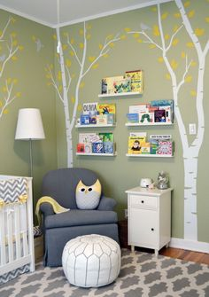 Gender-Neutral Nursery — Green Walls, White Birch Trees with Yellow Leaves — Wall Decals — Grey Birds — Art Shelves for Children's Books — Grey Glider Rocker — White Leather Moroccan Ottoman with Grey Stitching — Owl Pillow — Grey and White flat weave rug carpet — Shana Cunningham Designs www.shanacunningh...
