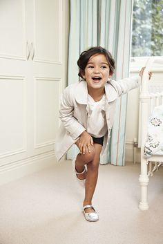 tan blazer and ivory bow-tied neck chiffon top paired with navy blue shorts and glitter flats.