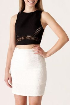 Black sleeveless textured crop top with crochet trim detail and back zipper closure. Paired here with a white textured skirt to complete the look.