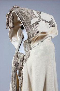 An embroidered felted wool cape, Middle Eastern, late 19th century, the elaborate hood couched and embroidered in silver threads, edged in braid and adorned with sequined tassels, similarly embroidered front panels  Provenance: Given to the vendor's ancestor Francis Lombardi by an Arab chieftain in the 1930s after a raid from Vercelli (North Italy) to Mogadishu.