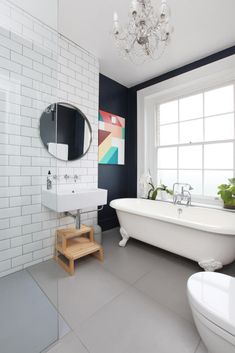 Modern art in a classic white bathroom bring some fun into the room!