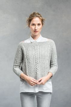 Architectural and completely modern in shape, this cropped pullover is a compelling knit and an eye-catching addition to any wardrobe. The front, back, and sleeves are simple quadrangles worked flat and seamed to achieve a wide, swingy shape with an open neckline and snugly fitted three-quarter-length sleeves. The interplay of twisted ribs, cables, and traveling …