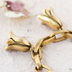 """Inspired by the tiny flowers that grow in the artist's garden during spring, this playful charm bracelet captures every detail of bluebells in bloom. From Orchard by J. Mavec.- Matte antique gold, brass- Lead and nickel free- Clean with solution of six parts warm water to one part ammonia or dishwashing liquid- Charm: 0.5""""W, 0.75""""L- Handmade in the USA8""""L"""