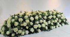 Een wit kleurig rouwstuk, gestoken op oasis.  Kistbedekking, willekeurig gestoken.   -Prijs: €250