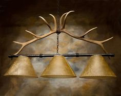 """The envy of decorators: a pair of real deer antlers to add to your rustic lodge look. The Buck Horn Pool Table Light is elegant in it's simplicity. The antlers are mounted on a decorated iron bar and hung by forged iron links. his light is hung by chain and includes three hand crafted 13"""" rawhide shades.    This light is UL listedT to hold three 60 watt bulbs. 13"""" Wide, 48"""" Long, 30"""" High. All our finishes are available."""