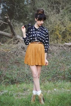 White frilly ankle socks, brown heels boots, short caramel pleated skirt, black and white patterned shirt