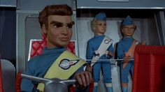 "Starting in the early Gerry and Sylvia Anderson made an indelible impact on the world of television with their groundbreaking production technique known as ""Supermarionation"". Joe 90, Thunderbirds Are Go, Movie Tv, Red Chairs, Set Design, Scarlet, Fandoms, Gray, Film"