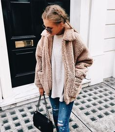 Cozy blush jacket over white top and blue jeans.