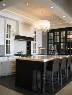 kitchens - tray ceiling black mirrored cabinet black kitchen island black turned legs beveled marble countertop black leather modern counter stools white kitchen cabinets glossy black countertop crystal chandelier