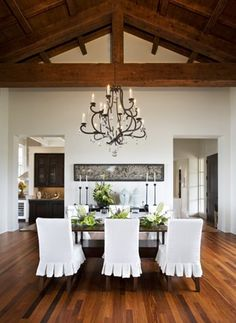 Chandelier and white slip covered chairs with huge wood farm style table.