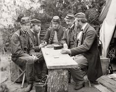 Civil War soldiers playing dominos on old wooden boxes, tree stumps,  wood plank...  (old wood, history)