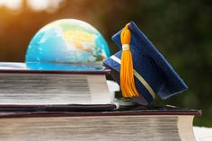 Blue Graduation Cap On Opening Textbook With Blur Of America Earth World Globe Model Map In Library Room Of Campus Overseas Education, Library Room, World Globes, Cabin Crew, Student Life, Travel And Tourism, Study Abroad, Textbook, Activities