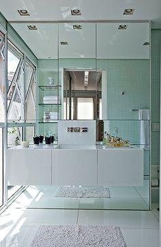 Ainda no projeto de Simone Mantovani, o banheiro de tons claros e com parede de espelhos dá a sensação de amplitude. Repare que a bancada suspensa com gavetões otimiza o espaço