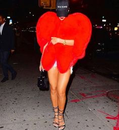 """""""Peace to fashion police I wear my heart On my sleeve let the runway start."""" The Bajan Beauty rocked a red heart shaped $15.000 YSL fox fur cape from Saint Laurent's 80s AW/2016 Autumn collection designed by the famous Hedi Slimane. She completed her look with a black baseball cap levis denim shorts and dsquared2 lace up heels. Does @badgalriri's outfit captured your heart?"""