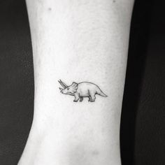 "1,5"" triceratops dinosaur tattoo on the ankle."