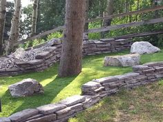 Why fight trying to get grass to grow under a Pine Tree. Artificial grass provides a green ground cover year round. Boulders and rock walls add character in this otherwise neglected corner of the yard. Minimal Maintenance by Creative Landscape & Design
