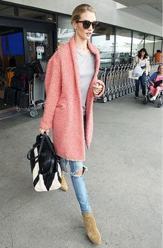 Rosie Huntington-Whiteley is wearing a grey t-shirt with distressed light blue jeans, tan suede booties, a pink coat, sunglasses and a black and white bag.