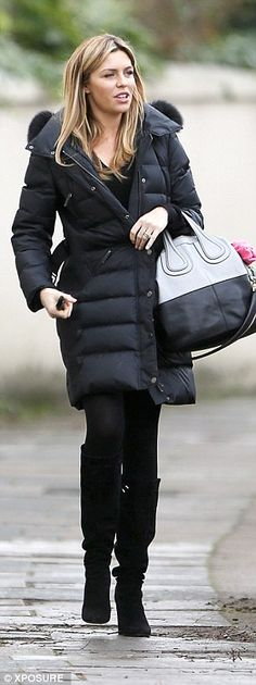City chic: She wore a large black padded coat, complete with a fur-trimmed hood and belt, ...