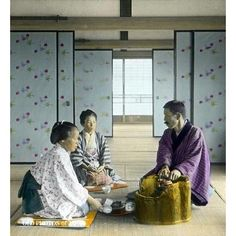1920's, Japan. Man and Two Women Having Tea Inside Room. Two women and a man in traditional clothing are sitting on zabuton (cushions) on tatami mats in a large room divided by fusuma (sliding doors) at what appears to be an inn. The man is warming his hands at a beautiful wooden hibachi used for keeping the water warm. The woman in the front appears to be preparing tea.