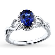 An oval lab-created sapphire framed in diamonds perches above a graceful band of 10K white gold in this pretty ring for her. The ring has a total diamond weight of 1/5 carat. Diamond Total Carat Weight may range from .18 - .22 carats.