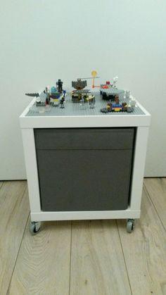 KALLAX open kast met DRONA bak. Lego plaat er op gelijmd. (eventueel) wieltjes er onder. Made by Laurie.