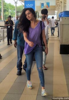 Shraddha Kapoor looks naturally beautiful as she goes makeup free in a casual look at Mumbai airport. She kept her hair open and paired a lavender v-neck top with ripped jeans and sneakers. via Voompla.com