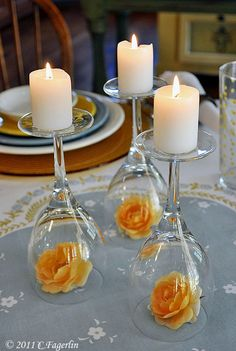 Upside down wine glasses with single rose buds beneath the glass and a candle on top at the base for a simple centerpiece or focal point.