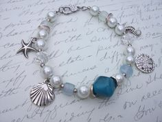 Ocean theme bracelet made of white glass pearls, crystals, resin and seaglass beads with silver plated seahorse, sand dollar, starfish and seashell charms in. Beaded Bracelets, Boutique, Etsy, Jewelry, Unique Jewelry, Bead, Jewlery, Jewerly, Pearl Bracelets