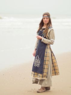 Viking outfit by Folktailor, photo by Orkfotografie.nl.  The apron dress seems to be sewn at the shoulders; it's harder to tell about the front cloth because her hair hides the brooches.